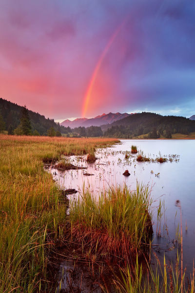 After heavy spring thunderstorm light shone through creating rainbow right in front of Soiernspitze at sunset in lake Gerold in Karwendel region of German alps, between Mittenwald and Garmisch-Partenkirchen