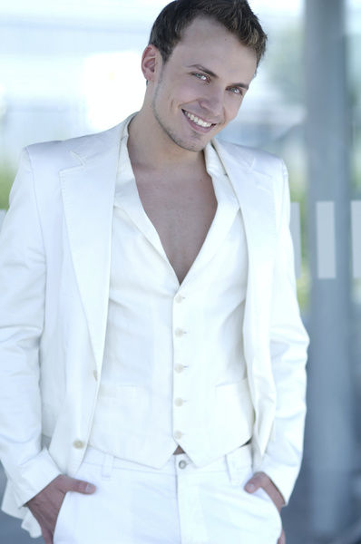 Young man wearing a white suit, smiling