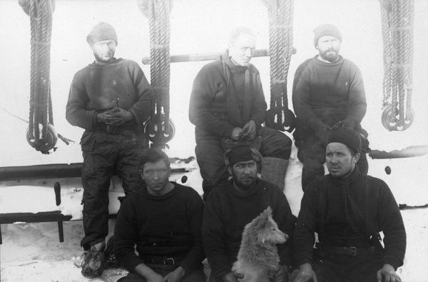 Photographer: Reginald William Skelton (1872-1956). Expedition: British National Antarctic Expedition 1901-04 (Discovery). Crew members of the ship Discovery. A group of six men seated on deck of the ship. One man holds a dog. Seated front left