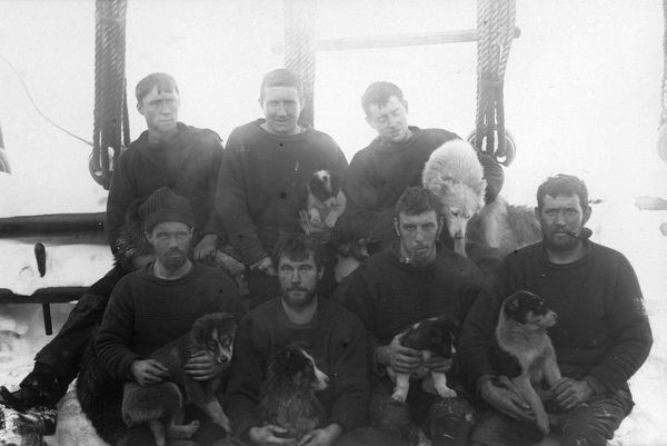 Photographer: Reginald William Skelton (1872-1956). Expedition: British National Antarctic Expedition 1901-04 (Discovery). Crew members of the ship Discovery. A group of seven men seated on deck of the ship. Six of the men are holding puppies