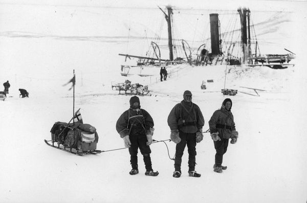 Photographer: Reginald William Skelton (1872-1956). Expedition: British National Antarctic Expedition 1901-04 (Discovery). Three men stand on the ice. They are harnessed to a fully loaded sledge The ship Discovery held fast in the pack ice behind
