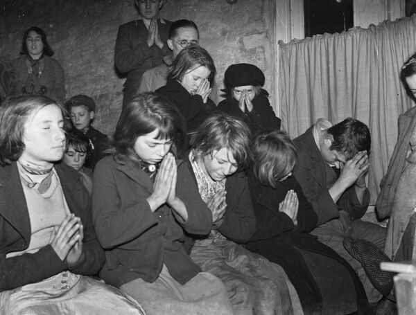 Gypsy children 's Sunday school in the cow shed in St Mary Cray .  Children praying .  1939 Travellers Romany Gypsy Gipsy gypsies Roma. social history