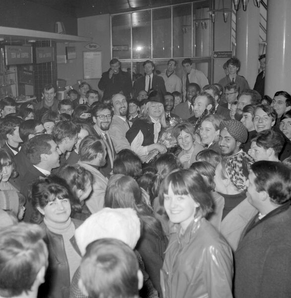 London : Fans surround folk singers Peter ( with glasses ), Paul and Mary as they hold an impromptu concert in the Queen 's Building at London Airport today on their arrival here from America