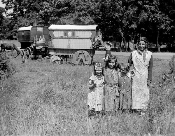 Romany gypsy girls posing outside their caravans on Epsom Downs during the Epsom race meeting .   1930s