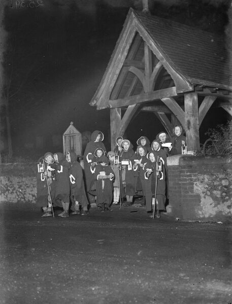 Young hooded carol singers singing by the lych gate outside Eynsford church, Kent