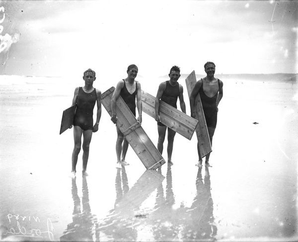 Four surfers with boards on beach. Photographer: Arthur William Jordan