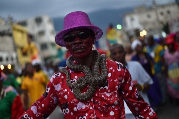 A reveler garlanded with snakes performs in the third and final day of Carnival in the capital of Haiti, Port-au-Prince, on February 28, 2017. Dancers, musician bands parade the streets in the center of Port-au-Prince. / AFP PHOTO / HECTOR RETAMAL