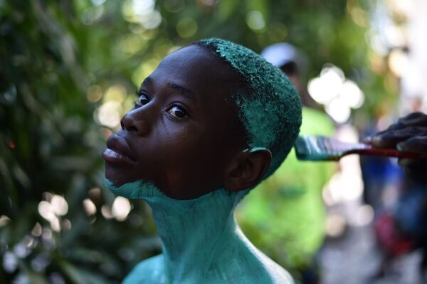 "A reveler is painted during preparations for the second day of the 2017 National Carnival Parade on February 27, 2017 in Les Cayes, southwestern Haiti. The name of the carnival for this year in Haitian creoleis ""Tet ansanb pou gran sid leve kanpe&quot"