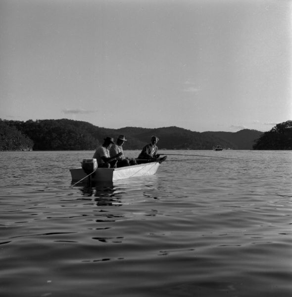 A black and white image of three men fishing in a small open boat (tinnie) on Pittwater, in Sydney's northern beaches. There are ripples in the water due to the movement of the boat, and the image is framed by the large, tree covered headlands