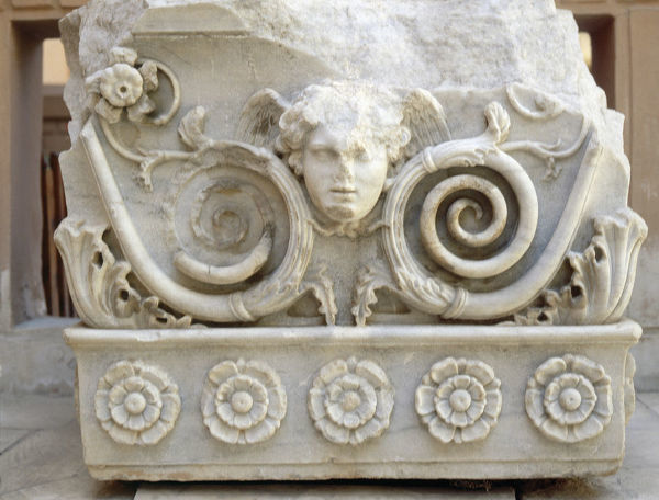 Relief carving depicting a winged head framed by plant