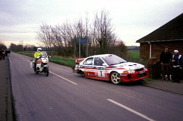 Tommi Makinen (FIN) Mitsubishi Lancer is pulled over by the British Police for running on the road with only three wheels, ending his rally and almost ending his championship hopes. World Rally Championship, Rally of Great Britain, Wales, UK