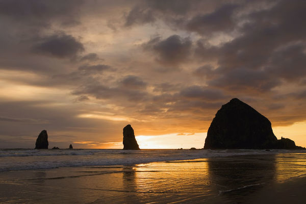 Silhouette Of Rock Formations And Haystack Rock At Sunset ...