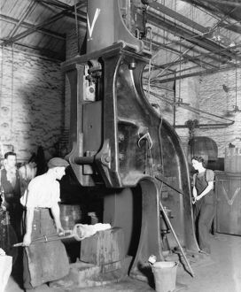 A man and woman carrying out work on a steam hammer during WW2, 1942