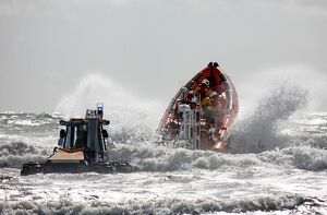 St Bees Atlantic 85 class inshore lifeboat Joy Morris MBE B-831 being launched from a trailer in rough seas.Four crew on board, bow high out of
