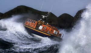 St Davids Tyne class lifeboat Garside 47-026 in rough seas. Three crew can be seen at the upper steering position. Lifeboat is breaking through a large wave and lots of