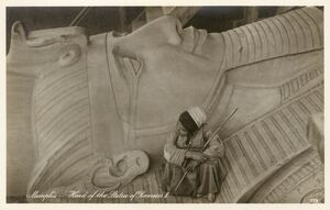 Egyptian boy sitting on the head of Rameses II
