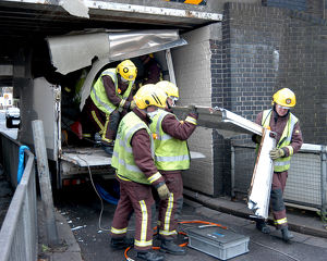 Firefighters working to remove van trapped under bridge