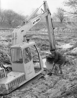 Man with mechanical digger in a muddy field