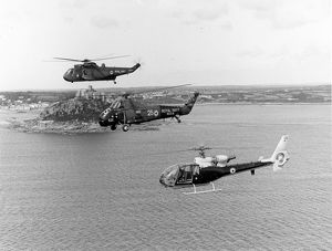 Three Royal Navy helicopters alongside St Michaels Mount