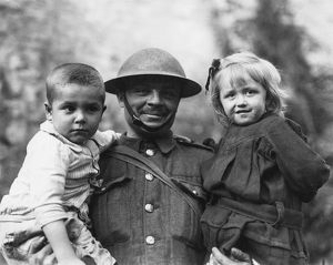 Soldier with two refugee children, Tournai, Flanders, WW1