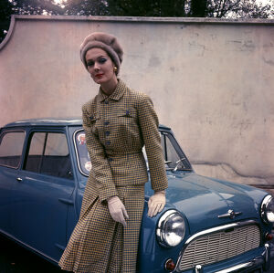 Woman in tweed suit posting with car