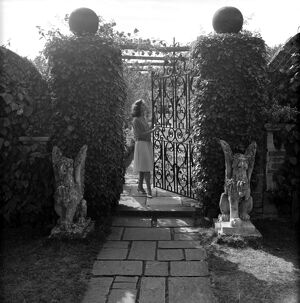 Wrought iron gate in a garden with female model