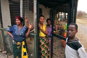 Local Women in front of a house behind cage protection