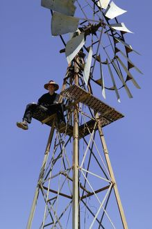 Windmill.Stockman sitting at top of windmill while