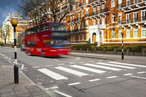 England, London, Abbey Road. A red London bus approaches the famous pedestrian crossing