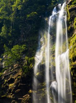 Laos, Ban Na Hin, Waterfall. Shafts of light pass through vegetation hanging to the