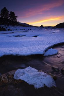 Scotland, Aberdeenshire, Linn of Dee. Pink sunset over the ice covered River Dee