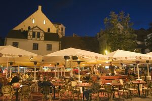 Al fresco dining at night in square of traditional buildings