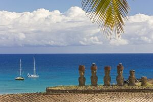 Anakena beach, yachts moored in front of the monolithic giant stone Moai statues