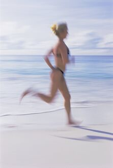 Blurred motion image of a woman jogging on the beach