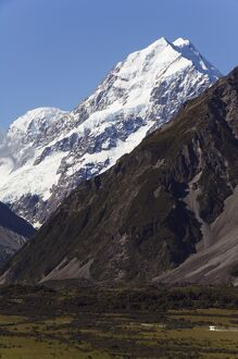 A camper van is dwarfed by Aoraki (Mount Cook)