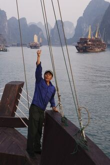 Crewman raises anchor on junk Ha Long Bay, Vietnam, Indochina, Southeast Asia, Asia