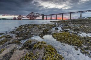 Dawn breaks over the Forth Rail Bridge, UNESCO World Heritage Site, and the Firth of Forth
