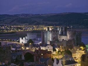 Floodlit Conwy Castle, UNESCO World Heritage Site, overlooking the town with the River Conwy estuary beyond at dusk, Gwynedd, North Wales, United