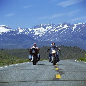 Harley Davidson bikers with snow-capped mountains in background, United States of America