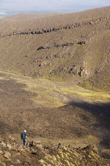 Hikers walking through a lava field on the Tongariro Crossing