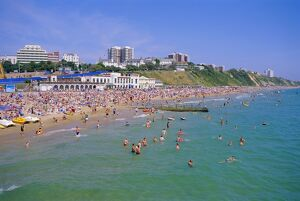 Holidaymakers in the sea and on the beach, Bournemouth, Dorset, England, UK