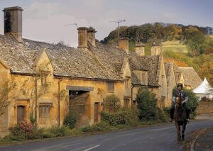 Horse and rider passing honey coloured stone cottages in the village of Stanton
