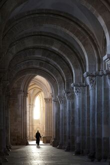 Interior north nave aisle with priest walking away, Vezelay Abbey, UNESCO World Heritage Site