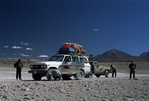 Landcruisers and tourists on jeep tour taking a break on Uyuni salt flat