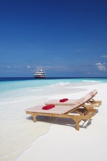 Lounge chairs on beach and yacht, Maldives, Indian Ocean, Asia