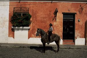 Man on horse in front of a typical painted wall