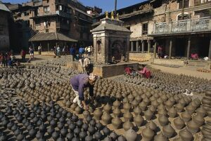 Man with rows of clay pots drying in Potters Square