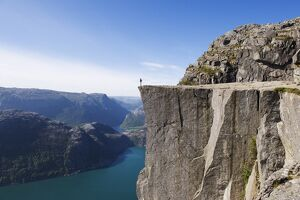 Man standing on Preikestolen (Pulpit Rock) above fjord, Lysefjord, Norway