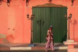Man walking past a pink house, St. Louis, Senegal, West Africa, Africa