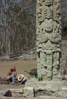 Two men excavating beside the Main Court Stela in the
